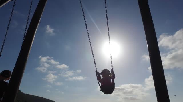 two kids enjoying the playpark swing - tyre swing stock videos & royalty-free footage