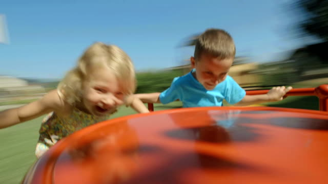 hd: two kids having fun on playground wheel - roundabout stock videos and b-roll footage