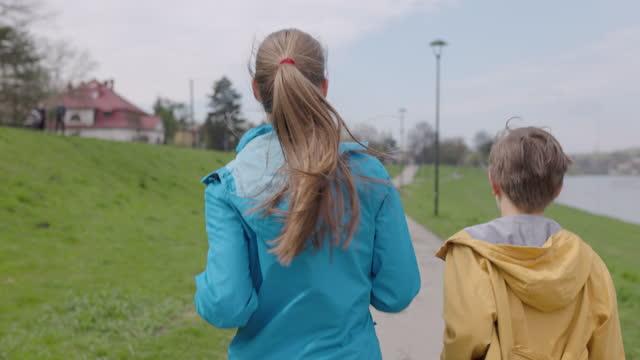 due bambini che fanno jogging sui viali del fiume - sunny video stock e b–roll