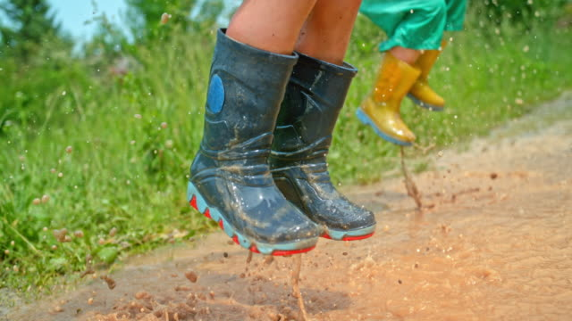 vídeos de stock e filmes b-roll de slo mo two kids jumping up and down in a muddy puddle wearing rain boots - travessura