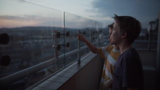vídeos de stock, filmes e b-roll de duas crianças na varanda olhando para o pôr do sol - vidro