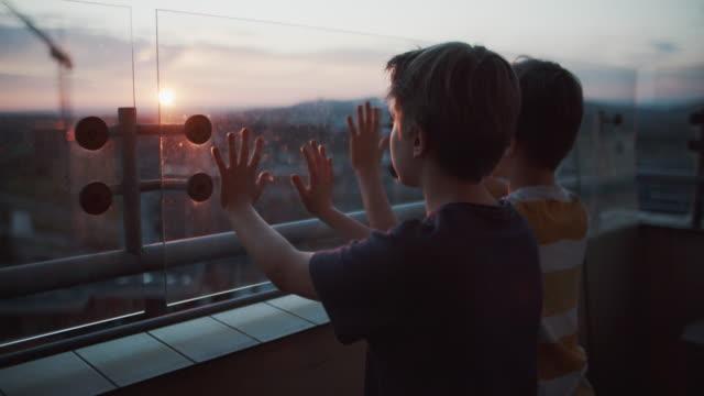 夕日を見ているバルコニーの2人の子供 - 負の感情点の映像素材/bロール