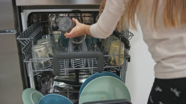 two kids placing dishes into the washing machine - lavastoviglie video stock e b–roll