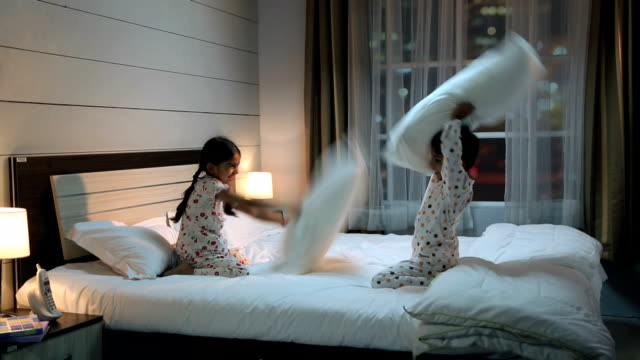 two kids playing pillow fight on the bed, delhi, india - 枕投げ点の映像素材/bロール