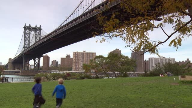 vídeos de stock e filmes b-roll de two kids run on the green grass at a park underneath the manhattan bridge in brooklyn dumbo. - ponte de manhattan