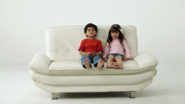 vídeos de stock, filmes e b-roll de two kids sitting on the couch  - barefoot
