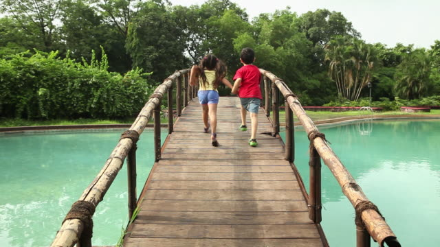 two kids walking on the footbridge  - haarzopf stock-videos und b-roll-filmmaterial