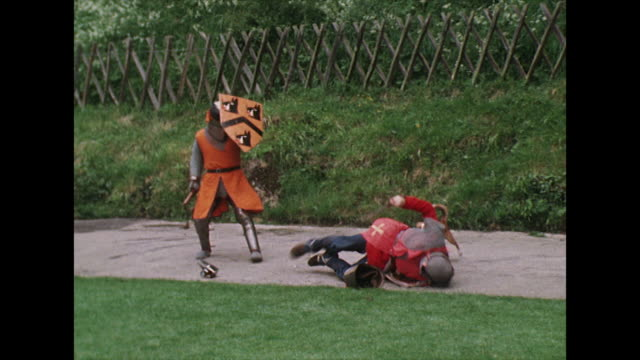 two knights fight with swords while a dog barks at them; 1975 - anno 1975 video stock e b–roll