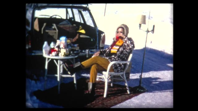 1969 two ladies have tailgate lunch on snowy street - sorpresa video stock e b–roll