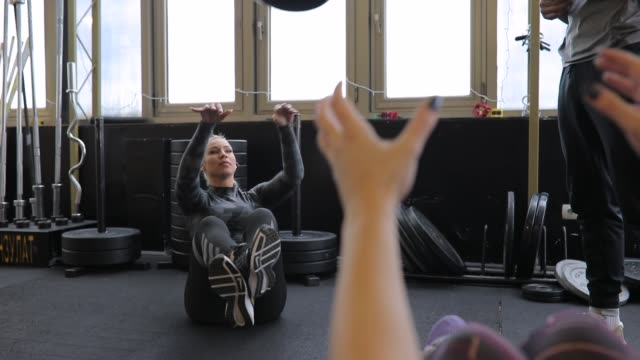 two ladies practicing with medicine ball in gym - instructor stock videos & royalty-free footage