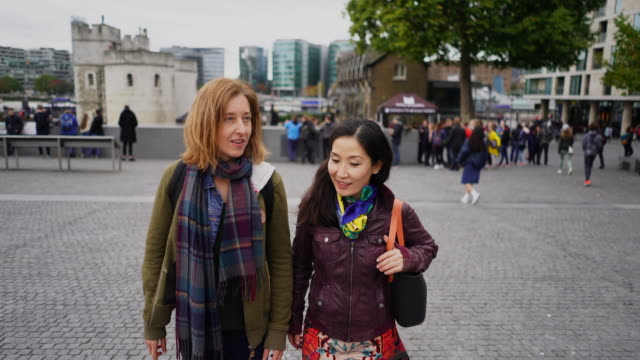 stockvideo's en b-roll-footage met two ladies walking and chatting. - koreaanse etniciteit