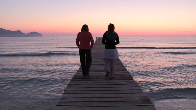 vídeos de stock e filmes b-roll de ws two lady roaming on jetty  at morning time / muro, mallorca, balearic isl, spain - docas