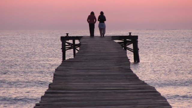 ms two lady roaming on jetty  at morning time / muro, mallorca balearic isl, spain - バレアレス点の映像素材/bロール