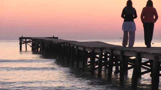 ms two lady roaming on jetty  at morning time / muro, mallorca balearic isl, spain - 腰に手を当てる点の映像素材/bロール