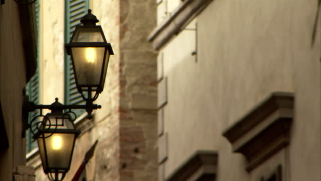 two lamps hang from a stone building in montepulciano, italy. available in hd. - montepulciano stock videos & royalty-free footage