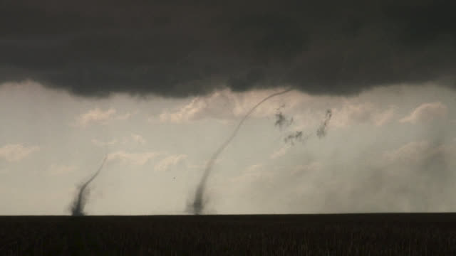 two landspout tornadoes spinning over rural field. - alley stock videos & royalty-free footage