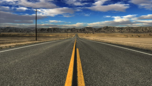 a two lane desert highway leads straight into the mountains. - 30 seconds or greater stock videos & royalty-free footage