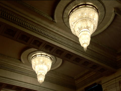 stockvideo's en b-roll-footage met two large dome shaped chandeliers hanging from decorated ceiling in ceaucescu's palace world's second largest building bucharest - jaar 2000 stijl