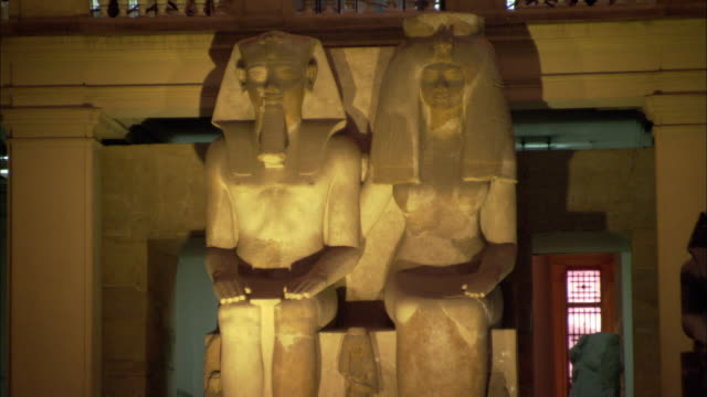 Two large Egyptian statues tower over museum patrons.