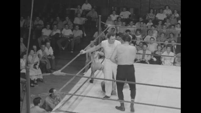 Two large men wrestling / littleperson wrestler standing on ropes / large men wrestling / large men wrestling and then two little people enter ring...