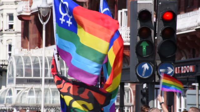 Two large pride flags wave in the breeze as they're carried down the street in the Brighton Gay Pride Parade 2017