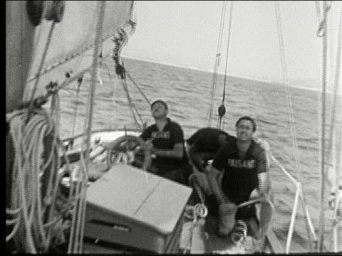 vidéos et rushes de two large yachts sailing in the open sea, sailboat race, schooner with full sails, sailors come about, crewman on deck pull in sails. two large... - équipe de voile