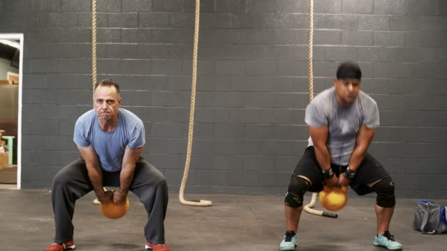 two latino athletes, the senior 55-years-old coach, and the younger man, doing the russian cannonball exercise with the heavyweight kettlebell. - 55 59 years stock videos & royalty-free footage