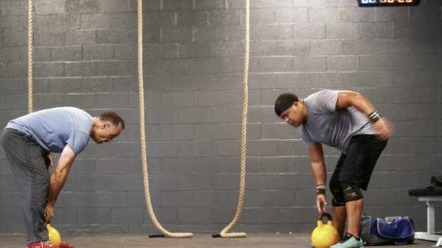 two latino athletes, the senior 55-years-old coach, and the younger man doing the powerlifting exercise with the heavyweight kettlebell. - 55 59 years stock videos & royalty-free footage