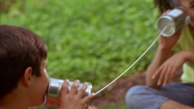 two latino children play using tin cans and string as a telephone. - brother stock videos & royalty-free footage
