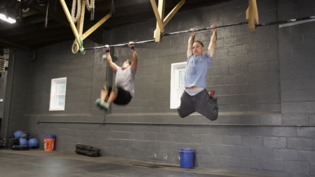 two latino men, the senior coach, and the young athlete, pulling-up on the horizontal bar in the gym during the hard workout - horizontal bar stock videos and b-roll footage