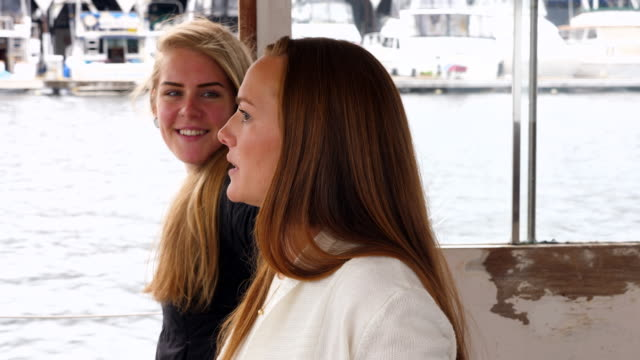 MS Two laughing friends looking out boat window on summer evening cruise