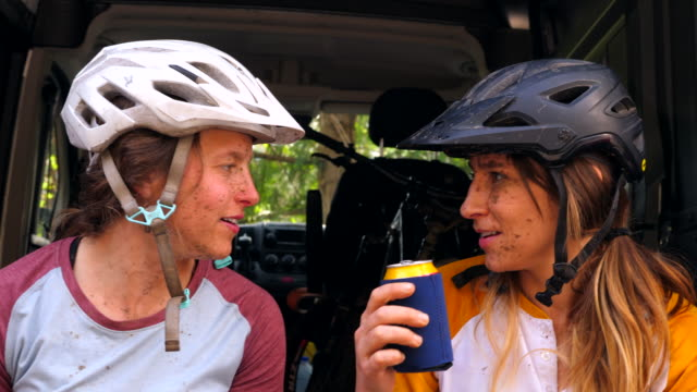 ms two laughing women in discussion while sitting on tailgate after muddy mountain bike ride - vuxen bildbanksvideor och videomaterial från bakom kulisserna