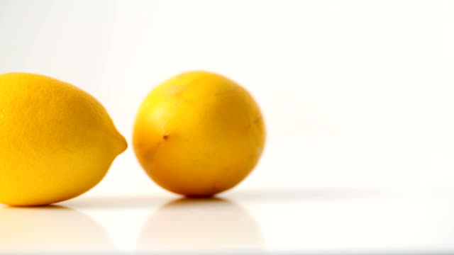 dolly: two lemons on white background - two objects stock videos & royalty-free footage