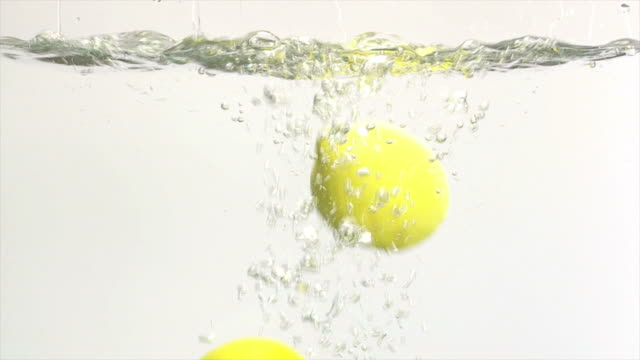 two lemons splashing into water slow motion - frische stock videos & royalty-free footage