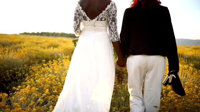 two lesbian brides walking in the flower field - wedding ring stock videos & royalty-free footage