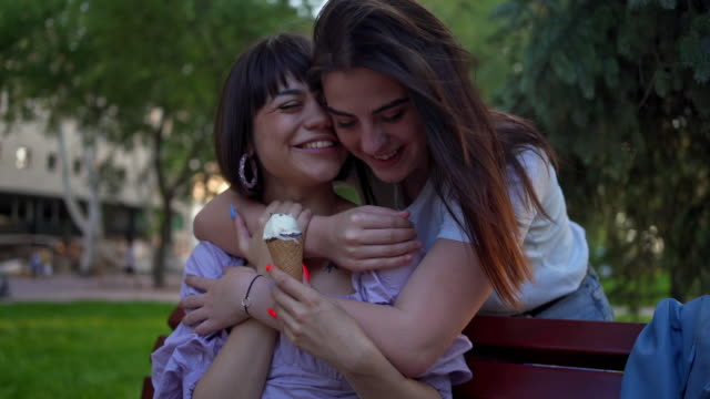two lesbian girls in love playing around on a bench outdoors - falling in love stock videos & royalty-free footage