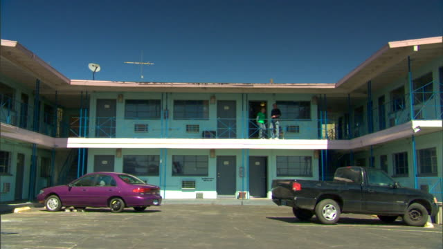 Two level motel rooms two cars parked in parking lot lower frame two unidentifiable people female male on balcony of second floor entering room