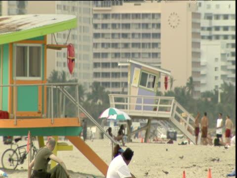 two lifeguard towers with sunbathers on beach miami - cabina del guardaspiaggia video stock e b–roll