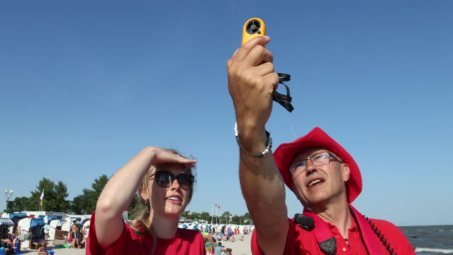 vidéos et rushes de two lifeguards are working to ensure the safety of people relaxing at the beach while one of the lifeguards is using an anemometer to measure the... - chapeau de soleil