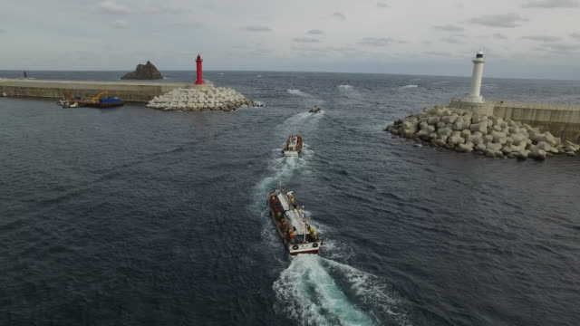 two lighthouses and fishing boats departing from jeodonghang port in ulleungdo island / ulleung-gun, gyeongsangbuk-do, south korea - fishing boat stock videos & royalty-free footage