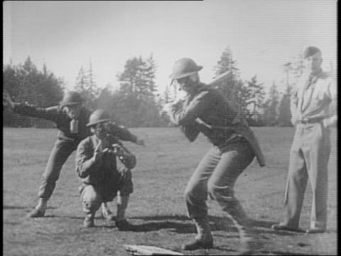 two lines of soldiers standing in front of army ambulance putting on gas masks / montage of soldiers in gas masks pitching hitting running and... - anno 1941 video stock e b–roll