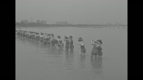 vídeos de stock e filmes b-roll de two lines of women in bathing suits walking along beach towards camera / male instructor shows women how to carry a drowning victim out of water / vs... - equipamento respiratório