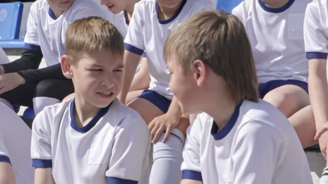 Two little boys in soccer uniform discussing something