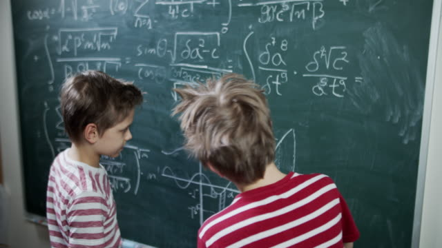 vidéos et rushes de deux petits garçons sur la leçon de maths discutant des maths - education