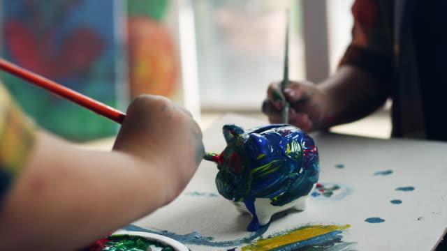 vídeos de stock, filmes e b-roll de dois rapazes pintando o cofrinho - arte e artesanato assunto