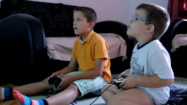 vídeos de stock e filmes b-roll de two little boys playing soccer game on gaming console and talking - irmão