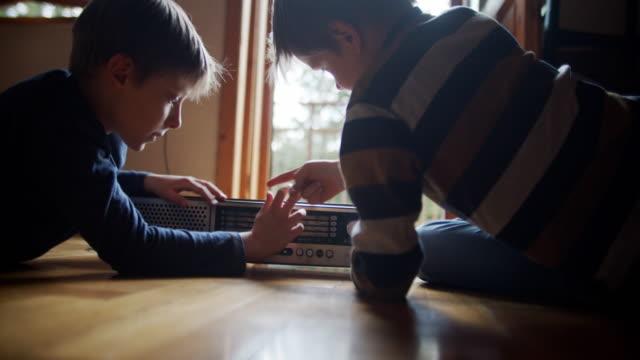 zwei kleine jungs spielen mit altem radio. - finden stock-videos und b-roll-filmmaterial