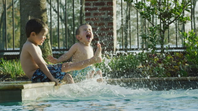 Two Little Caucasian Boys (a three and a five year-old) Sit by the Side of a Swimming Pool Kicking Their Feet in the Water While Smiling and Laughing on a Sunny Day with a Metal Fence Behind Them in Real Time