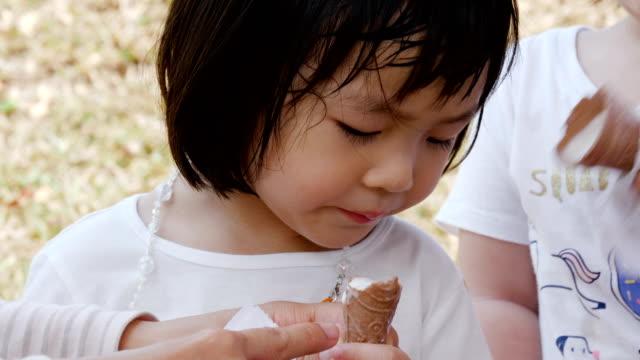 vidéos et rushes de deux petite fille manger la crème glacée - langue humaine