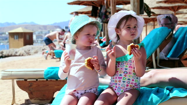 two little girls eat croissant on the beach. sharm el sheikh. egypt. - lounge chair stock videos & royalty-free footage